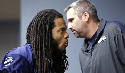 Seattle Seahawks' Richard Sherman, left, listens as Dave Pearson, team vice president of communications and broadcasting, whispers in his ear in the back of the room before an NFL football news conference Wednesday, Jan. 22, 2014, in Renton, Wash. The Seahawks play the Denver Broncos in the Super Bowl on Feb. 2. (AP Photo/Elaine Thompson)