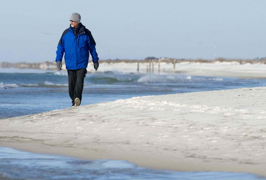 "Tim Carr takes a walk along the beach on Okaloosa Island in Fort Walton Beach, Fla., on Wednesday, Jan.  22, 2014, where the temperature was hovering in the low 30s. ""I don't like it when it's so cold,"" said Carr, ""but I've got a bunch of layers on."" (AP Photo/Northwest Florida Daily News, Devon Ravine)"