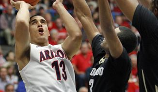 Arizona's Nick Johnson (13) shoots for two against the defense of Colorado's Xavier Talton (3) and Xavier Johnson, far right, in the first half of an NCAA college basketball game, Thursday, Jan. 23, 2014 in Tucson, Ariz. (AP Photo/John Miller)