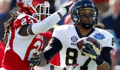 Vanderbilt wide receiver Jordan Matthews (87) catches a pass over Houston defensive back Trevon Stewart (23) for a touchdown during the first half of the BBVA Compass Bowl NCAA college football game on Saturday, Jan. 4, 2014, in Birmingham, Ala. (AP Photo/Butch Dill)