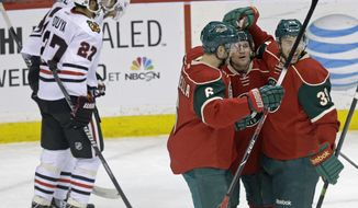 Minnesota Wild's Matt Cooke, right center, is congratulated on his goal by Marco Scandella and Nate Prosser, right, as Chicago Blackhawks' Johnny Oduya, left, of Sweden, and Michal Rozsival, skate to their bench in the first period of an NHL hockey game, Thursday, Jan. 23, 2014, in St. Paul, Minn. (AP Photo/Jim Mone)