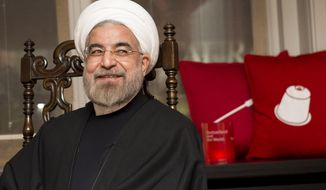Iranian President Hassan Rouhani, smiles as he meets President of the Swiss Confederation Didier Burkhalter during a bilateral meeting on the sideline of the 44.  Annual Meeting of the World Economic Forum, WEF, in Davos, Switzerland, Thursday, Jan. 23, 2014. (AP Photo/Keystone,Jean-Christophe Bott)