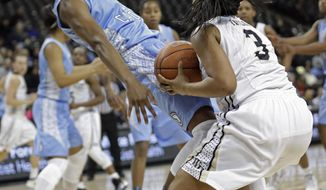 North Carolina's Diamond DeShields, left, is knocked down by Wake Forest's Ataijah Taylor, right, during the first half of an NCAA college basketball game in Winston-Salem, N.C., Thursday, Jan. 23, 2014. Taylor was charged with a foul. (AP Photo/Chuck Burton)
