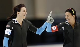 FILE - In this Dec. 28, 2013, file photo, the United States' Heather Richardson, left, celebrates her first place finish with second place finisher Brittany Bowe after their women's 500-meter race at the U.S. Olympic speedskating trials in Kearns, Utah.  These former inline skaters maintain a close relationship off the ice, even while pushing each other to greater heights as they head to the Winter Olympics. (AP Photo/Rick Bowmer, File)