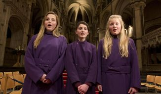 In this Wednesday, Jan. 22, 2014 photo, choristers Poppy Braddy, left, Chloe Chawner, centre, and Abby Cox sing during an interview with the Associated Press in Canterbury Cathedral, Canterbury, England, as the first all female choir at the cathedral rehearses prior to their debut on Jan. 25. The pure, high voices of the choir soar toward the vaulted ceiling of Canterbury Cathedral as they have for more than 1,000 years. Just one thing is different - these young choristers in their purple cassocks are girls, and their public debut at Evensong on Saturday will end centuries of all-male tradition. Canterbury is not the first British cathedral to set up a girls' choir, but as mother church of the 80 million-strong Anglican Communion - one struggling with the role of women in its ranks - its move has special resonance.(AP Photo/Alastair Grant)