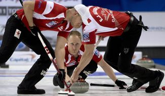 FILE  In this April 6, 2013, file photo, Canada skip Brad Jacobs, center, makes a shot as second, E.J. Harnden, right, and lead Ryan Harnden sweep during a page 3-4 playoff draw against Denmark at the World Men's Curling Championship in Victoria, British Columbia. After a breakthrough year in 2013 in which his rink became Canadian champion before romping through Olympic trials, Jacobs heads to the Sochi Games as the big favorite for the gold medal.  (AP Photo/The Canadian Press, Jonathan Hayward, File)