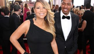 """FILE - This Jan. 18, 2014 file photo shows Mariah Carey, left, and Nick Cannon at the 20th annual Screen Actors Guild Awards in Los Angeles. Scholastic announced Thursday, Jan. 23, that it has acquired the couple's """"Roc and Roe's Twelve Days of Christmas,"""" a picture story scheduled for release this fall. Illustrated by A.G. Ford, the book is a holiday tale featuring twins Moroccan and Monroe, whom Carey gave birth to in 2011. (Photo by Matt Sayles/Invision/AP, File)"""