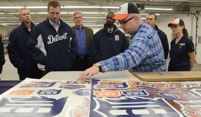 Dan Izzo explains the Fathead making process to Detroit Tiger pitcher Max Scherzer, left, and other members of the Tigers organization during a visit by the Tigers in Battle Creek, Mich., Thursday, Jan. 23, 2014. Tigers players and coaches visited various sites in the state on their two-day caravan meeting with baseball fans. (AP Photo/Battle Creek Enquirer, John Grap)