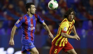 Levante's David Barral duels for the ball with Barcelona's Carles Puyol during their la Copa del Rey soccer match at the Ciutat de Valencia stadium in Valencia, Spain, Wednesday Jan. 22, 2014. (AP Photo/Alberto Saiz)