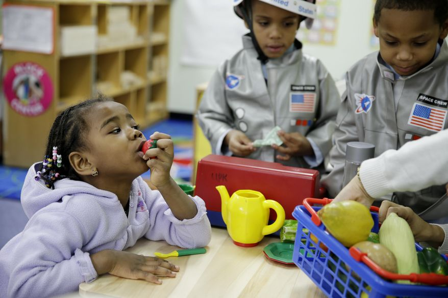 In this Tuesday, Jan. 21, 2014 photo, Oumou Balde, 4, left, chews on a plastic strawberry at the Sheltering Arms Learning Center in New York. Balde participated in a program that was produced in conjunction with Sesame Street to educate children about nutrition and health. (AP Photo/Seth Wenig)