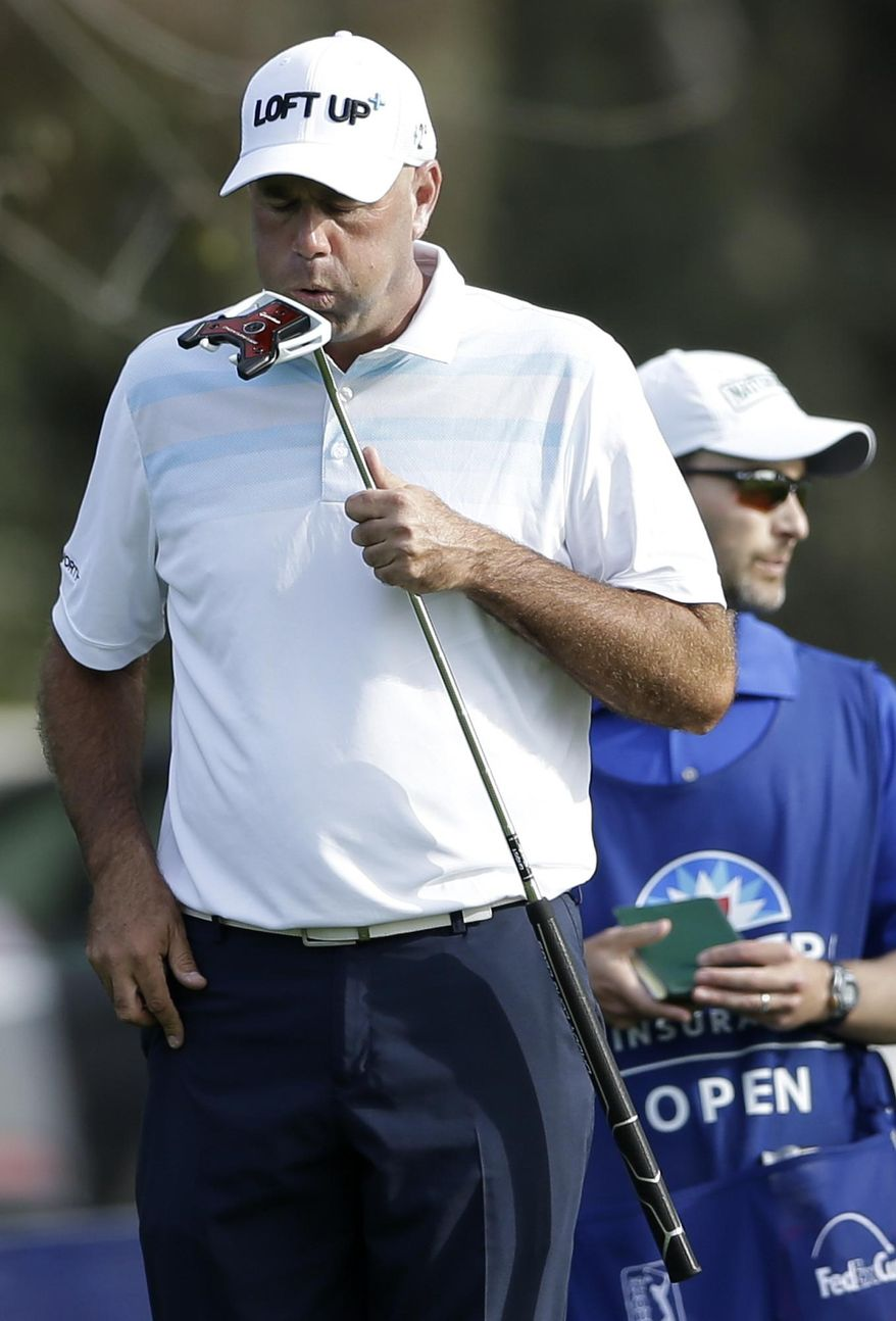 Stewart Cink, left, blows on his putter before sinking a putt for birdie as caddie Matt Hall, right, waits on the 17th hole of the North Course during the first round of the Farmers Insurance Open golf tournament Thursday, Jan. 23, 2014, in San Diego. (AP Photo/Gregory Bull)