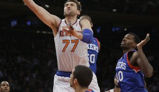 New York Knicks' Andrea Bargnani (77), of Italy, drives past Philadelphia 76ers' Dewayne Dedmon (30) and Michael Carter-Williams (1) during the first half of an NBA basketball game, Wednesday, Jan. 22, 2014, in New York.  (AP Photo/Frank Franklin II)