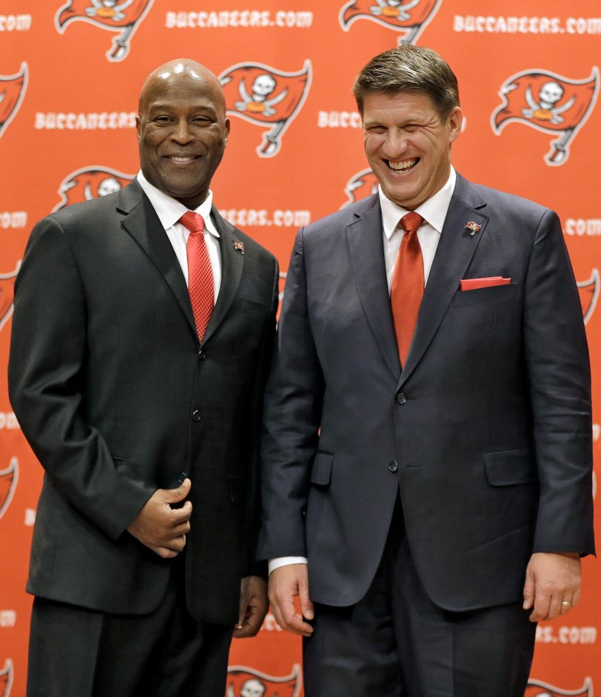 New Tampa Bay Buccaneers general manager Jason Licht, right, smiles as he poses for a photo with new head coach Lovie Smith during an NFL football news conference Thursday, Jan. 23, 2014, in Tampa, Fla. Licht becomes the fifth general manager in team history.  He takes over a team that hasn't made the playoffs since 2007. (AP Photo/Chris O'Meara)