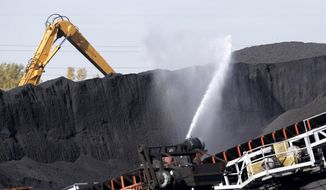 FILE - In this Oct. 25, 2013 file photo, petroleum coke, or petcoke, is watered down where it is stored along the Calumet River on Chicago's southeast side.  The Pollution Control Board is scheduled to meet Thursday, Jan. 23, 2014, in Chicago to consider Gov. Pat Quinn's proposed emergency regulations for petroleum coke. Quinn says he's responding to complaints from Chicago residents that petroleum coke piling up on the city's southeast side is a health and environmental threat. (AP Photo/Charles Rex Arbogast, File)