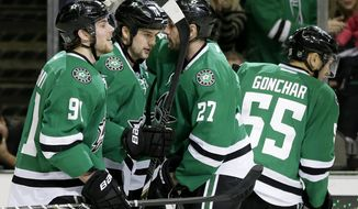 Dallas Stars' Tyler Seguin (91), Aaron Rome (27) and Sergei Gonchar (55) congratulate Jamie Benn (14) on his goal in the first period of an NHL hockey game against the Toronto Maple Leafs, Thursday, Jan. 23, 2014, in Dallas. (AP Photo/Tony Gutierrez)