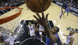 Oklahoma City Thunder's Kevin Durant, center, scores against the San Antonio Spurs during the first half of an NBA basketball game, Wednesday, Jan. 22, 2014, in San Antonio. (AP Photo/Eric Gay)