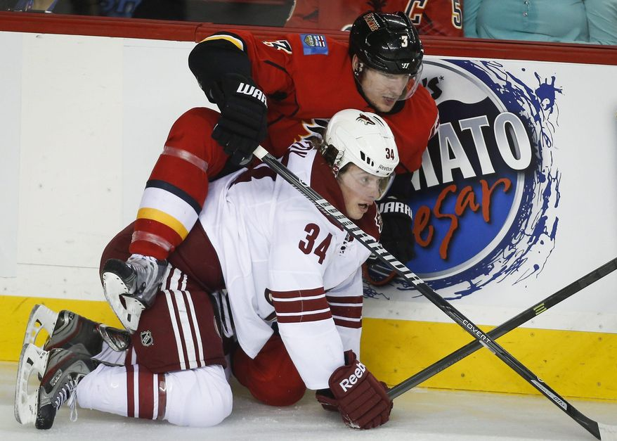 Phoenix Coyotes' Tim Kennedy, right, gets tangled up with Calgary Flames' Ladislav Smid, from the Czech Republic, during second period NHL hockey action in Calgary, Canada, Wednesday, Jan. 22, 2014. (AP Photo/The Canadian Press, Jeff McIntosh)