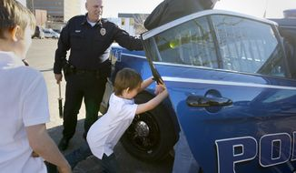 Dorian Layton, 6, shoves a robbery suspect played by Detective Jeremy Tremel into the patrol car after Layton helped solve a staged investigation on Tuesday afternoon, Jan. 21, 2014 at City Hall in Casper, Wyo.  Layton, who has a nontreatable tumor on his brain stem, was named honorary police chief for the day and given the opportunity to solve a crime scenario. (AP Photo/Casper Star-Tribune, Dan Cepeda)
