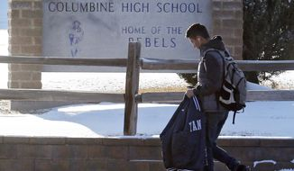 A student leaves Columbine High School after a lockout was lifted at the school in Littleton, Colo., on Thursday, Jan. 23, 2014. Columbine High School, where a school shooting left 13 people dead in 1999, went on high security alert after receiving a series of threatening phone calls, law enforcement said Thursday.(AP Photo/Ed Andrieski)