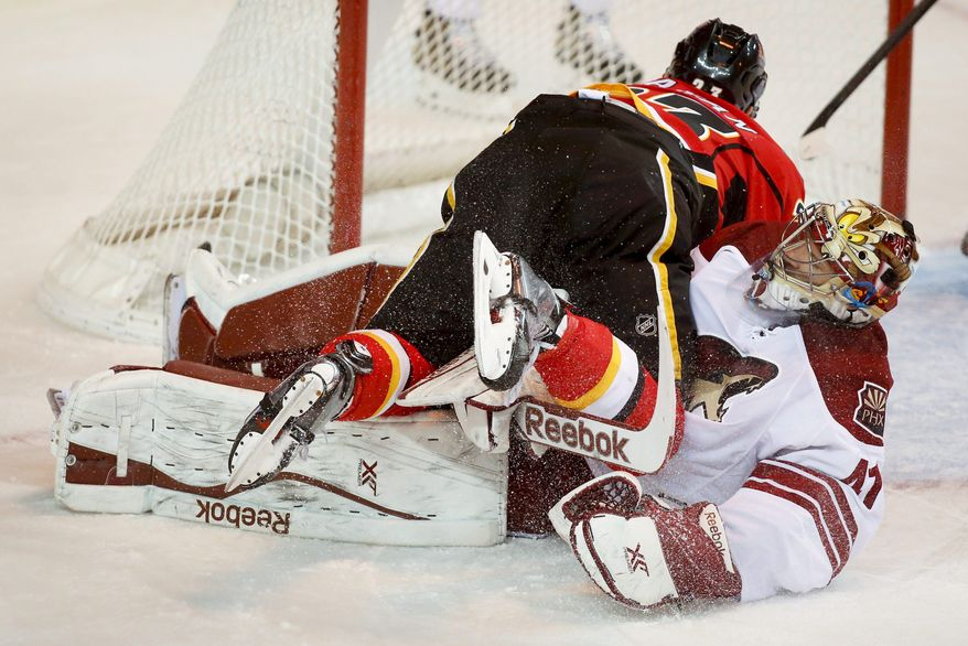 Phoenix Coyotes goalie Mike Smith, right, looks on as Calgary Flames' Sean Monahan crashes over him after scoring during first period NHL hockey action in Calgary, Canada, Wednesday, Jan. 22, 2014. (AP Photo/The Canadian Press, Jeff McIntosh)