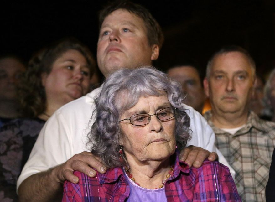 Gayle Gaddis, mother of slain Houston police officer Guy Gaddis is comforted by her son Edwin outside the prison walls after the execution of Mexican national Edgar Tamayo Wednesday, Jan. 22, 2014, in Huntsville, Texas. Tamayo was convicted of killing Gaddis 20 years ago. (AP Photo/Pat Sullivan)