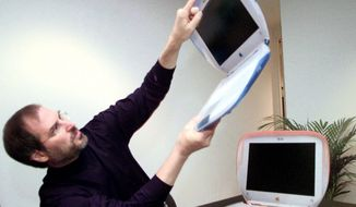 """** FILE ** In this Wednesday, July 21,1999, file photo, Steve Jobs, founder and then-acting CEO of Apple Computer Inc., holds up one of the company's new consumer laptops called an """"iBook"""" after his keynote address at the Macworld Expo in New York. (AP Photo/Bebeto Matthews)"""