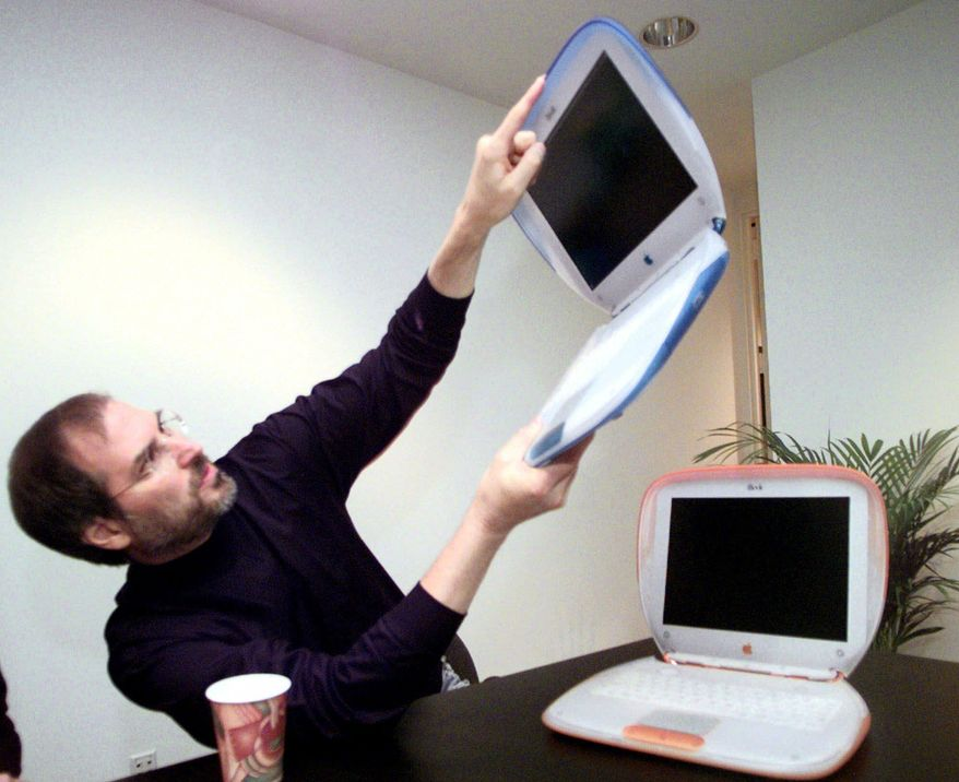 "** FILE ** In this Wednesday, July 21,1999, file photo, Steve Jobs, founder and then-acting CEO of Apple Computer Inc., holds up one of the company's new consumer laptops called an ""iBook"" after his keynote address at the Macworld Expo in New York. (AP Photo/Bebeto Matthews)"