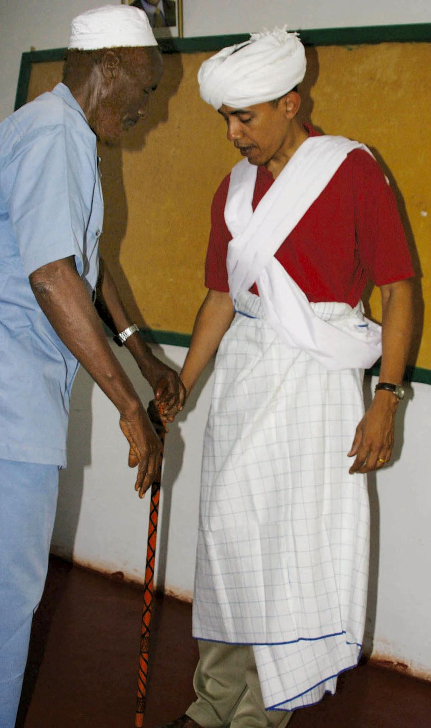 **FILE** Then-Sen. Barack Obama (right) is dressed as a Somali Elder by Sheikh Mahmed Hassan during his visit in 2006 to Wajir, a rural area in northeastern Kenya, near the borders with Somalia and Ethiopia. (Associated Press)