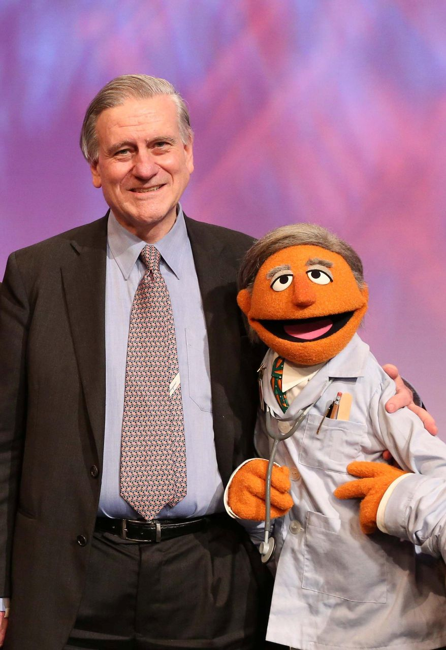 """In this May 1, 2012 photo provided by Sesame Workshop, Dr. Valentin Fuster, a cardiologist at New York's Mount Sinai Hospital, stands with a Muppet character based on him, """"Dr. Ruster,"""" in the Sesame Street studios in the Queens borough of New York. Fuster, who teamed up with Sesame Street on a project to improve kids' health, has shown progress in a study in Colombia. In 2014, the project is planned to launch in New York in what sponsors hope will be a first step to fight childhood obesity nationwide. (AP Photo/Sesame Workshop, Richard Termine)"""
