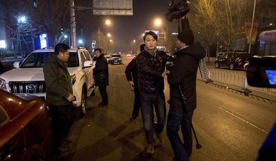 Chinese policemen try to prevent journalists from interviewing Zhang Qingfang, inside the white SUV, a lawyer of legal scholar and founder of the New Citizens movement Xu Zhiyong near the No. 1 Intermediate People's Court, where Xu stood trial, in Beijing Wednesday, Jan. 22, 2014. (AP Photo/Andy Wong)