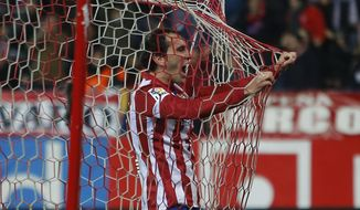 Atletico's Diego Godin celebrates his goal during a Copa del Rey soccer match between Atletico de Madrid and Athletic Bilbao at the Vicente Calderon stadium in Madrid, Spain, Thursday, Jan. 23, 2014. (AP Photo/Andres Kudacki)