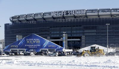 A tractor plows snow off the parking lot of MetLife Stadium near a tent which will serve as an access point into Super Bowl XLVIII as crews removed snow following a snow storm, Wednesday, Jan. 22, 2014, in East Rutherford, N.J.  Super Bowl XLVIII, which will be played between the Denver Broncos and the Seattle Seahawks on Feb. 2, will be the first NFL title game held outdoors in a city where it snows. (AP Photo/Julio Cortez)