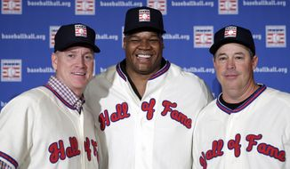 FILE - In this Jan. 9, 2014, file photo, former Atlanta Braves pitchers Tom Glavine, left and Greg Maddux, right, pose with Chicago White Sox slugger Frank Thomas after a press conference in New York, announcing their election to the Baseball Hall of Fame. Maddux will not have any logo on his cap in his Hall of Fame plaque, the Hall said Thursday, Jan. 23, 2014. Glavine's will have a Braves logo, while Thomas' will have a White Sox logo. (AP Photo/Kathy Willens, File)