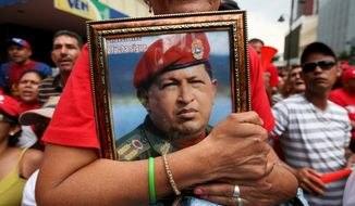 FILE - In this April 19, 2013 file photo, a supporter of Venezuela's newly sworn-in President Nicolas Maduro holds a picture of late President Hugo Chavez during Maduro's inauguration in Caracas, Venezuela. Civil rights and liberties around the world declined for the eighth straight year, dragged down by the Egyptian military's coup, Venezuela clinging to authoritarianism and Russia's crackdown on opposition groups, according to a pro-democracy watchdog group. (AP Photo/Gil Montano, File)