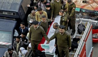 Egyptian police gather around the coffin of a policeman during the funeral of one of several policemen killed after masked gunmen opened fire at a police checkpoint in el-Wassta district in the province of Bani Suief, south of the Egyptian capital, Cairo, Egypt, Thursday, Jan. 23, 2014. (AP Photo/Mohammed Asad)