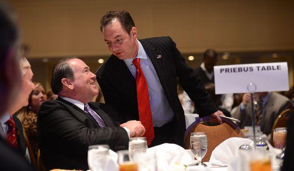 RNC Chairman Reince Priebus, center, speaks with Mike Huckabee, left, over lunch at the Republican National Committee's annual winter meeting, Washington, D.C., Thursday, January 23, 2014. (Andrew Harnik/The Washington Times)