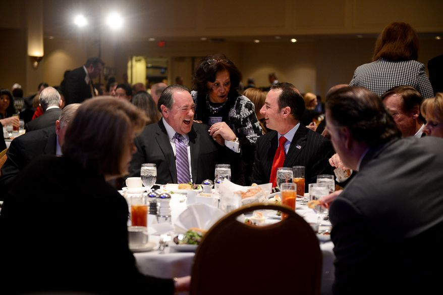 Millie Hallow of Maryland, center, shares a laugh with RNC Chairman Reince Priebus, right, and Mike Huckabee, left, during lunch at the Republican National Committee's annual winter meeting, Washington, D.C., Thursday, January 23, 2014. (Andrew Harnik/The Washington Times)
