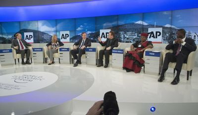 """AP Senior Managing Editor Michael Oreskes, left, moderates a discussion with, from left, Save the Children International CEO Jasmine Whitbread, British Prime Minister David Cameron, rock star Bono, Nigerian Finance Minister Ngozi Okonjo-Iweala and Tidjane Thiam, Prudential group chief executive during a panel discussion  """"The Post-2015 Goals: Inspiring a New Generation to Act"""", the fifth annual Associated Press debate, at the World Economic Forum in Davos, Switzerland, Friday, Jan. 24, 2014.  (AP Photo/Michel Euler)"""