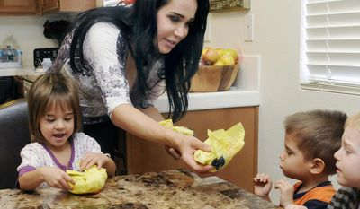 FILE - In this Oct. 23, 2012, file photo, Nadya Suleman feeds her children, from left Maliyah, Jonah and Noah, at their new home in Palmdale, Calif. Suleman picked Biblical names for all eight of her octuplets: Noah, Jonah, Jeremiah, Josiah, Isaiah, Makai, Nariyah and Maliyah. All have the same middle name, Angel.  (AP Photo/Antelope Valley Press, Ron Siddle, File)