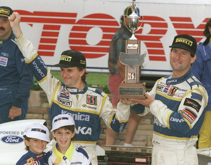 In this 1996 file photo, Wayne Taylor, top left, along with his two sons Jordan, lower left, 5, and Ricky,7, with co-driver Jim Pace celebrate winning the IMSA championship in Victory Lane at Daytona International Speedway in Daytona Beach, Fla. (AP Photo/Daytona Beach News-Journal, Nigel Cook)
