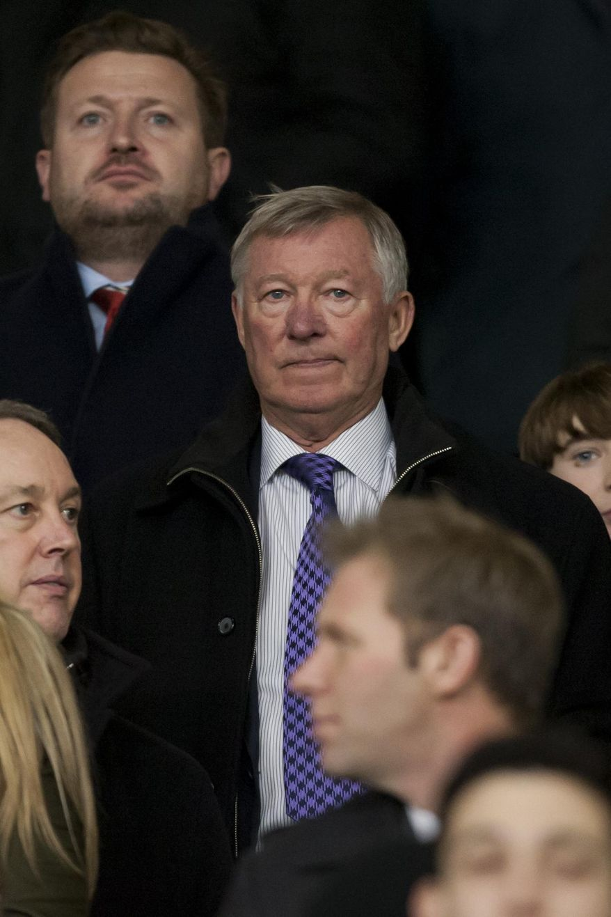 Manchester United's former manager Alex Ferguson takes his seat before the team's English League Cup semifinal second leg soccer match against Sunderland at Old Trafford Stadium, Manchester, England, Wednesday Jan. 22, 2014. (AP Photo/Jon Super)