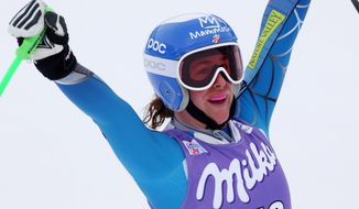 Stacey Cook, of the US, celebrates her fifth place in an an alpine ski World Cup women's downhill, in Cortina D'Ampezzo, Italy, Friday, Jan. 24, 2014. (AP Photo/Armando Trovati)