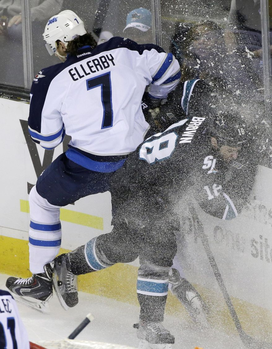 Winnipeg Jets' Keaton Ellerby (7) collides against the boards with San Jose Sharks' Mike Brown (18) during the first period of an NHL hockey game Thursday, Jan. 23, 2014, in San Jose, Calif. (AP Photo/Marcio Jose Sanchez)