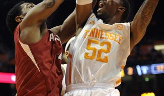 Tennessee guard Jordan McRae (52) goes to the basket against Arkansas forward Coty Clarke (4) during the first half of an NCAA college basketball game in Knoxville, Tenn., on Wednesday, Jan. 22, 2014. Tennessee won 81-74. (AP Photo/Knoxville News Sentinel, Adam Lau)