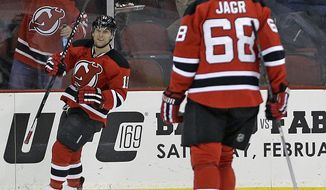 New Jersey Devils right wing Stephen Gionta, left, celebrates after scoring a goal against the Washington Capitals on an assist by Jaromir Jagr (68), of the Czech Republic, during the first period of an NHL hockey game, Friday, Jan. 24, 2014, in Newark, N.J. (AP Photo/Julio Cortez)
