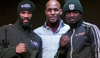 IBF junior welterweight champion Lamont Peterson, left, and a Canada's Dierry Jean, right, pose with pose with Bernard Hopkins, center, from Golden Boy Promotion, during a boxing news conference, Thursday, Jan. 23, 2014 in Washington. Peterson is slated to defend his title against Jean on Saturday at the DC Armory. (AP Photo/Pablo Martinez Monsivais)