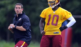 FILE - In this Aug. 16, 2012, file photo, Washington Redskins quarterback coach Matt LaFleur, left, works with quarterback Robert Griffin III during NFL football training camp in Ashburn, Va. Notre Dame head football coach Brian Kelly announced Friday, Jan. 24, 2014, that they hired LaFleur as the team's new quarterbacks coach. (AP Photo/Richard Lipski, File)