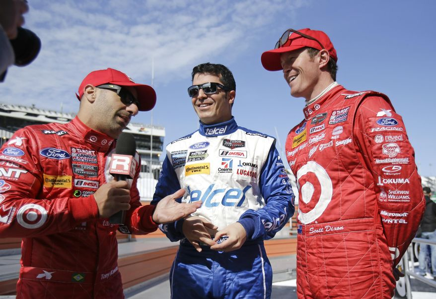 Tony Kanaan, left, of Brazil, interviews Memo Rojas, center, of Mexico, and Scott Dixon, of New Zealand after a practice for the IMSA Series Rolex 24 hour auto race at Daytona International Speedway in Daytona Beach, Fla., Friday, Jan. 24, 2014. (AP Photo/John Raoux)