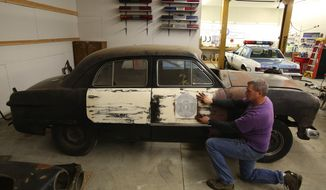 In a Jan. 13, 2014 photo, Seattle police Officer Jim Ritter, of the Seattle Metropolitan Police Museum, holds an original side-door decal that is being used in the restoration project on the 1949 Washington State Patrol car. The restoration work is being done in Ellensburg, Wash. (AP Photo/The Seattle Times, Ken Lambert)  SEATTLE OUT; USA TODAY OUT; MAGAZINES OUT; TELEVISION OUT; NO SALES; MANDATORY CREDIT TO: THE SEATTLE TIMES