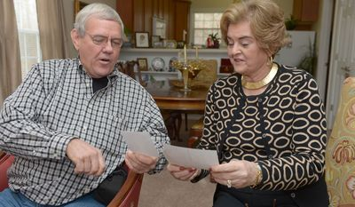 In this Monday Dec. 30, 2013 photo, Don Cowan, left, and his former 8th grade teacher Linda Harris, right, look at photos during a reunion at Harris' home in Elon, N.C. (AP Photo/Burlington Times-News, Sam Roberts)